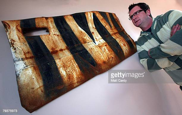 John Chalmers looks at a door on his living room wall that he is saved from a wrecked car that was left in a quarry and painted by the guerrilla...