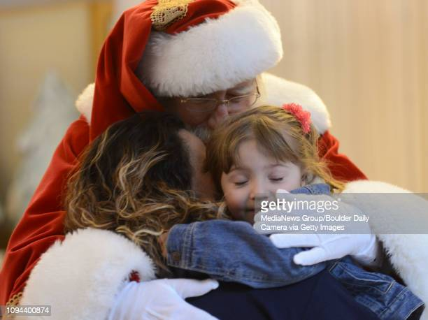 John Chilson aka Santa Claus hugs Evony Ortiz and her grandmother Angela Mendias while they were visiting Santa's Photo Village at Twin Peaks Mall...