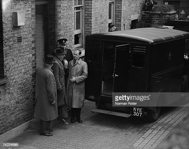 John Christie hides his face as he leaves West London Police Court after a remand hearing 8th April 1953 Christie is accused of his wife's murder at...
