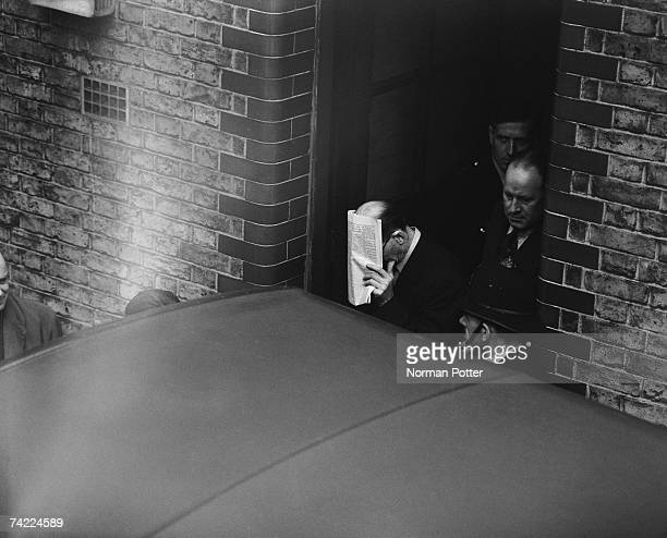 John Christie hides his face as he leaves West London Police Court after a remand hearing 15th April 1953 Christie is accused of his wife's murder at...