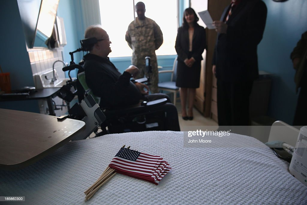 John Cincar, 62, (L), raises his right hand while repeating the oath of allegiance to the United States during a ''homebound'' naturalization ceremony on October 25, 2013 in the Queens borough of New York City. Cincar, who was born in Yugoslavia and moved to the United States in 1965, has been a quadripelegic since falling at home in 2011 and now lives in the Midway Nursing Home. U.S. Citizenship and Immigration Services (USCIS), performs such on site naturalization ceremonies for immigrants with health issues and disabilities who have limited mobility. With his new American citizenship, Cincar says he plans to apply for a U.S. passport and, after further physical rehabilitation, hopes to travel back to his village near Belgrade, Serbia to visit family members he has not seen since his youth. He served in the U.S. Army from 1969-1972 as a supply clerk in Germany.