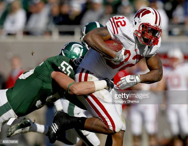 John Clay of the Wisconsin Badgers tries for extra yards during a third quarter run in front of Adam Decker of the Michigan State Spartans on...