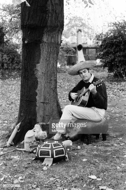 John Cleese relaxing in the garden of his home in Holland Park With John are his cats as he sits beneath a tree and plays the guitar to a stuffed...