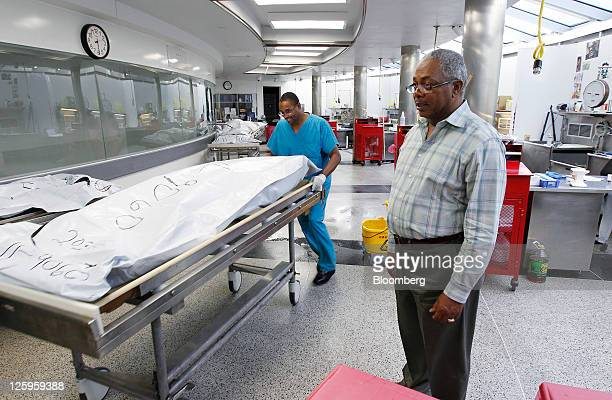 John Collins an autopsy technician left pushes a body past Albert Samuels chief investigator with the Wayne County Medical Examiner's office at the...