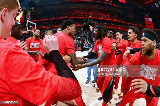 John Collins and DeAndre' Bembry of the Atlanta Hawks huddle with their teammates before the game against the Charlotte Hornets on February 9 2019 at...