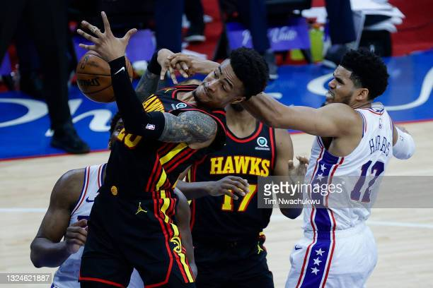 John Collins of the Atlanta Hawks and Tobias Harris of the Philadelphia 76ers reach for a rebound during the third quarter during Game Seven of the...