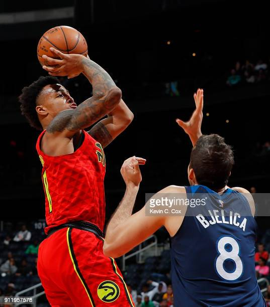 John Collins of the Atlanta Hawks attempts a shot against Nemanja Bjelica of the Minnesota Timberwolves at Philips Arena on January 29 2018 in...