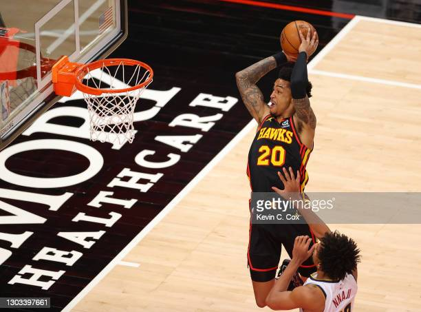 John Collins of the Atlanta Hawks catches an alley-oop for a dunk against Zeke Nnaji of the Denver Nuggets during the first half at State Farm Arena...