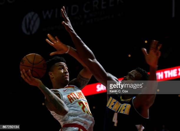 John Collins of the Atlanta Hawks drives against Paul Millsap of the Denver Nuggets at Philips Arena on October 27 2017 in Atlanta Georgia NOTE TO...