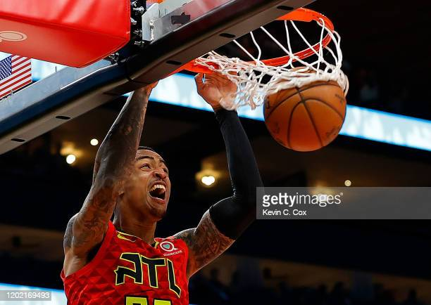 John Collins of the Atlanta Hawks dunks against Davis Bertans of the Washington Wizards in the second half at State Farm Arena on January 26, 2020 in...