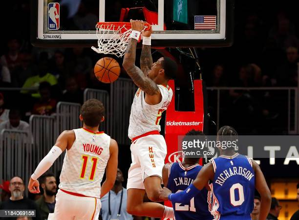 John Collins of the Atlanta Hawks dunks an alley-oop pass from Trae Young against Joel Embiid and Josh Richardson of the Philadelphia 76ers in the...