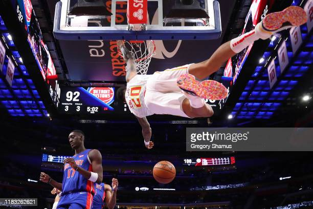 John Collins of the Atlanta Hawks dunks next to Tony Snell of the Detroit Pistons during the second half at Little Caesars Arena on October 24 2019...