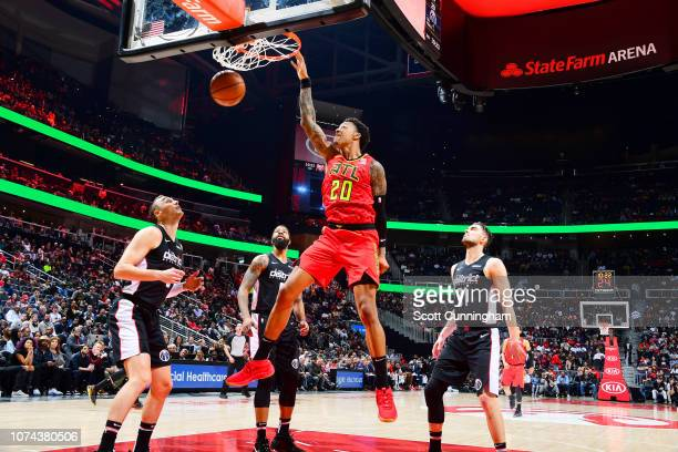 John Collins of the Atlanta Hawks dunks the ball against the Washington Wizards on December 18 2018 at State Farm Arena in Atlanta Georgia NOTE TO...