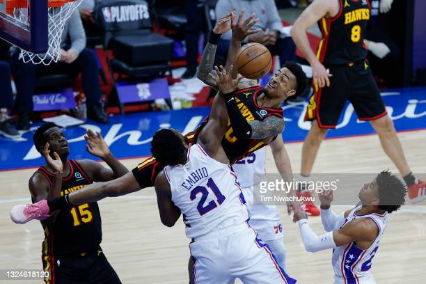 John Collins of the Atlanta Hawks gets a rebound against Joel Embiid of the Philadelphia 76ers during the fourth quarter during Game Seven of the...