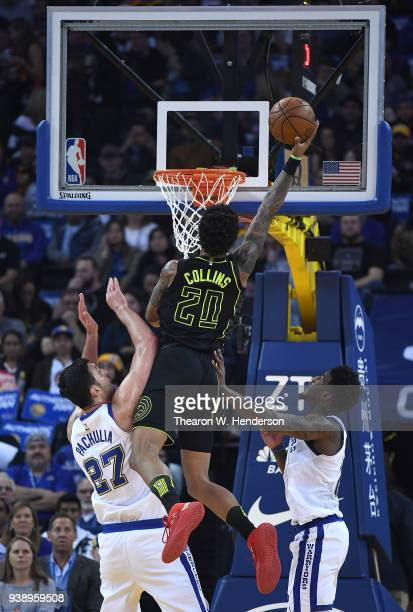 John Collins of the Atlanta Hawks goes in for a layup over Jordan Bell and Zaza Pachulia of the Golden State Warriors during an NBA basketball game...