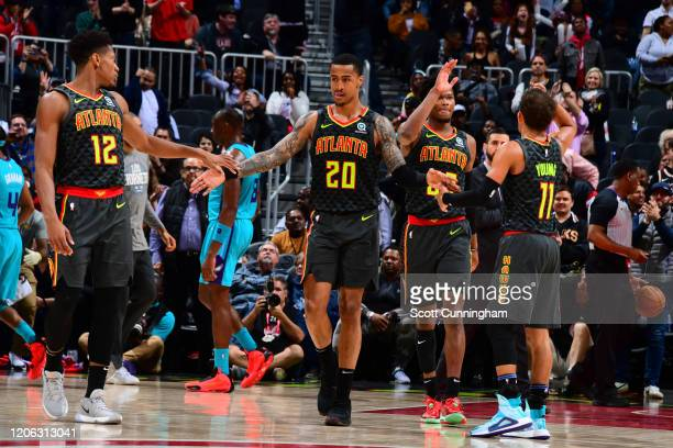 John Collins of the Atlanta Hawks high fives his teammates during the game against the Charlotte Hornets on March 9, 2020 at State Farm Arena in...