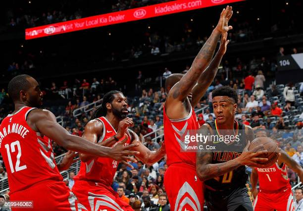 John Collins of the Atlanta Hawks is defended by PJ Tucker Nene Hilario and Luc Mbah a Moute of the Houston Rockets at Philips Arena on November 3...