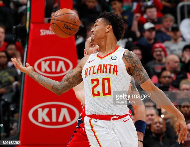 John Collins of the Atlanta Hawks loses the ball against Marcin Gortat of the Washington Wizards at Philips Arena on December 27 2017 in Atlanta...