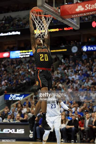 John Collins of the Atlanta Hawks makes a slam dunk against the Dallas Mavericks in the second half at American Airlines Center on October 18 2017 in...