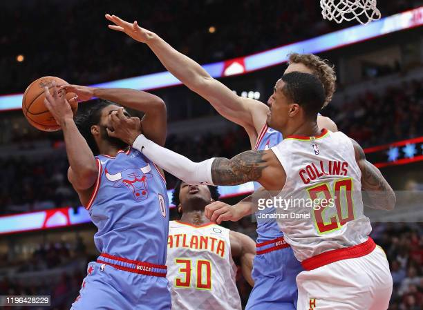 John Collins of the Atlanta Hawks smacks Coby White of the Chicago Bulls in the face as he rebounds at the United Center on December 28 2019 in...