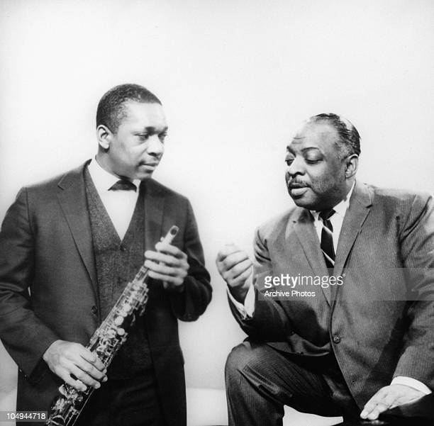 John Coltrane holds a saxophone while talking with Count Basie circa 1950