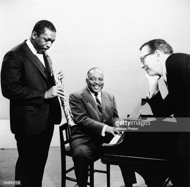 John Coltrane plays a saxophone while Count Basie plays the piano as another man looks on circa 1950