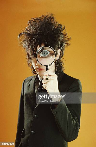 John Cooper Clarke holding a magnifying glass up to his eye CBS Records studio London circa 1977
