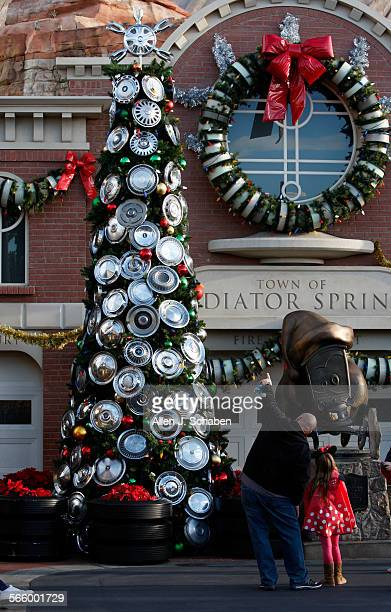 John Corlett and daughter Taylor Corlett of San Diego view a large Christmas tree decorated with hubcaps amid the Christmas and holiday makeover of...