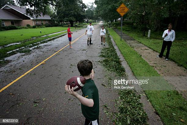 John Corry plays catch in the street with friends and family shortly after Hurricane Gustav passed through September 1, 2008 in Lafayette, Louisiana....