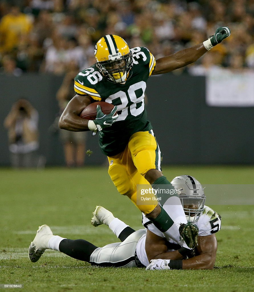 John Crockett #38 of the Green Bay Packers is tackled by Cory James #57 of the Oakland Raiders in the third quarter of a preseason game at Lambeau Field on August 18, 2016 in Green Bay, Wisconsin.
