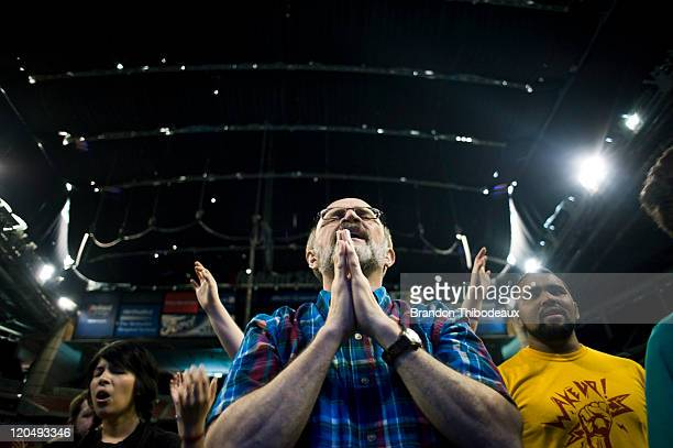 John Crouse stands praying in a crowd of attendees as they dance and sing during the opening musical act of the nondenominational prayer and fasting...