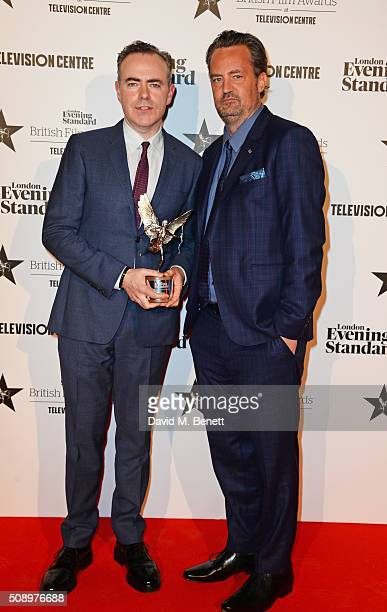 John Crowley accepting the Best Film award for 'Brooklyn' and presenter Matthew Perry pose in front of the Winners Boards at the London Evening...