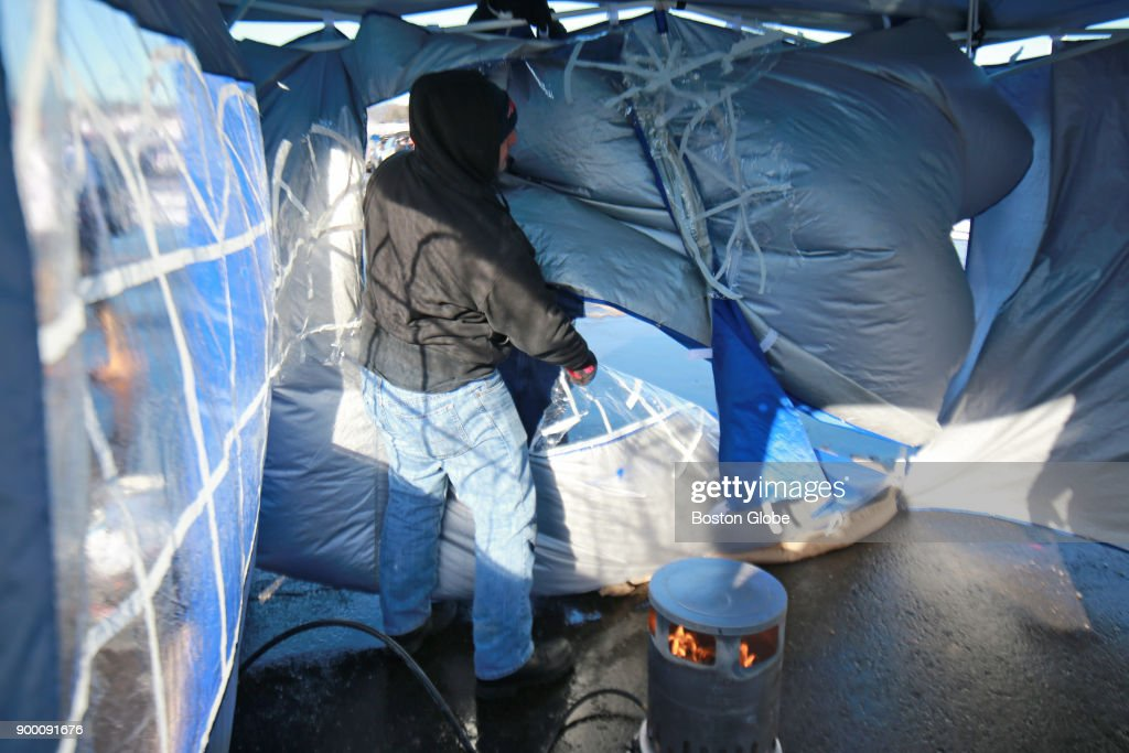 John Cucchiara of Billerica fixes his tent after the plastic split as soon as it was & New York Jets Vs New England Patriots at Gillette Stadium Pictures ...