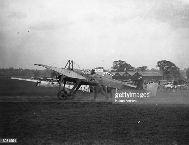 John Cyril Porte a pilot for the British Deperdussin Company taxies a 100 hp two seat Deperdussin monoplane whilst helpers guide it across the grass