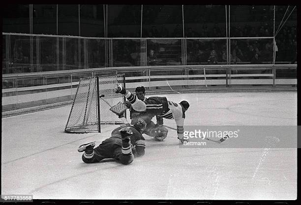 John Dale of St Paul Minnesota of the US Olympic Ice Hockey team goes flying over Russian goalie Victor Konovalenko and another unidentified Russian...
