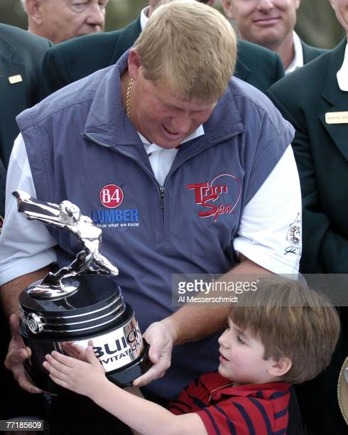 John Daly and fouryearold son Austin examine the winner's trophy at Torrey Pines Golf Course site of the Buick Invitational during finalround play...
