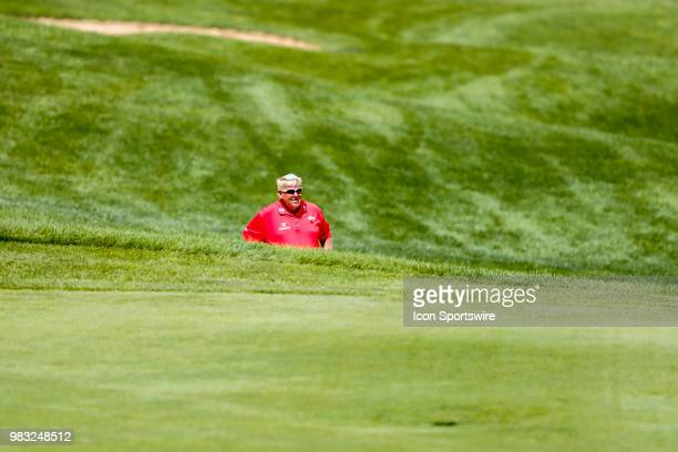 John Daly considers his options after putting his tee shot into a bunker on eighteen during the final round of the American Family Insurance...