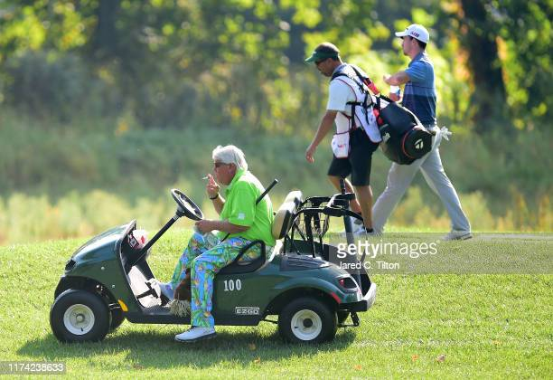 John Daly drives away from the second tee as Nick Taylor of Canada and his caddie walk the second hole during the first round of A Military Tribute...