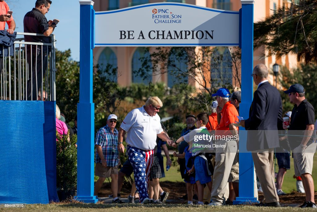 John Daly fist-bumps a young fan as he arrives on the first tee before the final round of the PNC Father/Son Challenge at The Ritz-Carlton Golf Club on December 17, 2017 in Orlando, Florida.