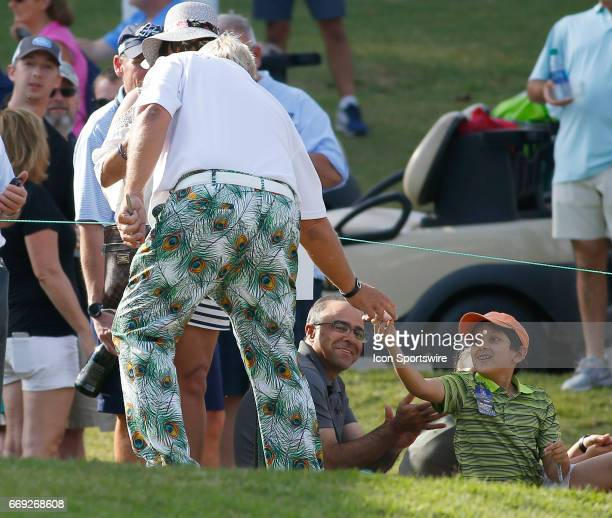 John Daly hands a young fan an autographed golf ball after finishing the final round of the Mitsubishi Electric Classic tournament at the TPC...