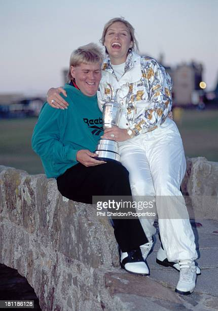 John Daly of the United States holding the trophy with his wife Paulette on the Swilcan Bridge after winning the British Open Golf Championship held...