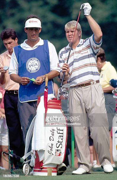 John Daly of the United States selects a club watched by his caddie during the US PGA Championship held at the Inverness Club in Ohio circa August...