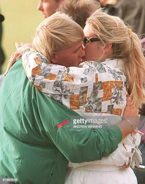 John Daly of the US receives a kiss from his wife Paulette after sinking his putt on the 18th green to go into a playoff with Italian Costantino...