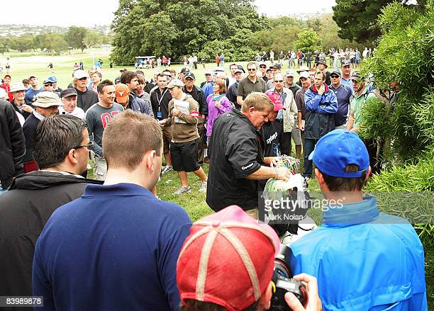 John Daly of the USA is surrounded by onlookers after he threw a spectator's camera against a tree on the ninth hole during the first round of the...