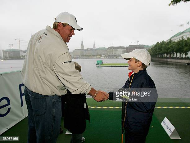 John Daly of USA shakes hands with Christoph Schierholz who had a hole in one at the beat the pro competition before the rain delayed first round of...