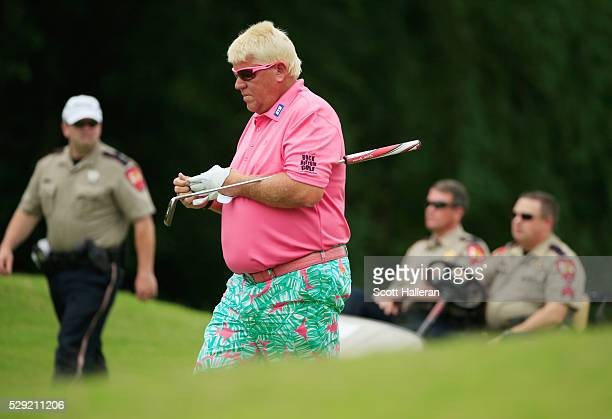 John Daly walks on the second hole as law enforcement officers look on during the final round of the Insperity Invitational at The Woodlands Country...