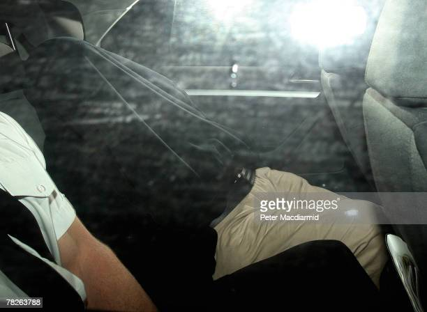 John Darwin lies under a coat as he is escorted by police leaving a police station on December 5, 2007 in Basingstoke, England. Mr Darwin has been...