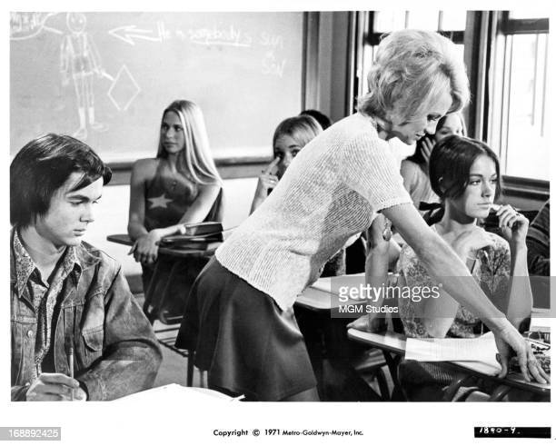 John David Carson and Margaret Markov sit in class as he is distracted by Angie Dickinson who is leaning over JoAnna Cameron in a scene from the film...