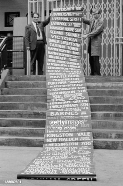 John Day and Michael Beamish unrolling a scroll of London bus destination names UK 13th May 1976
