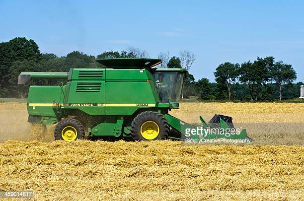 john deere combine in wheat field - john deere stock pictures, royalty-free photos & images